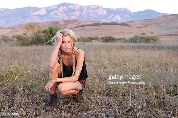 Beautiful blond teen squatting down in field