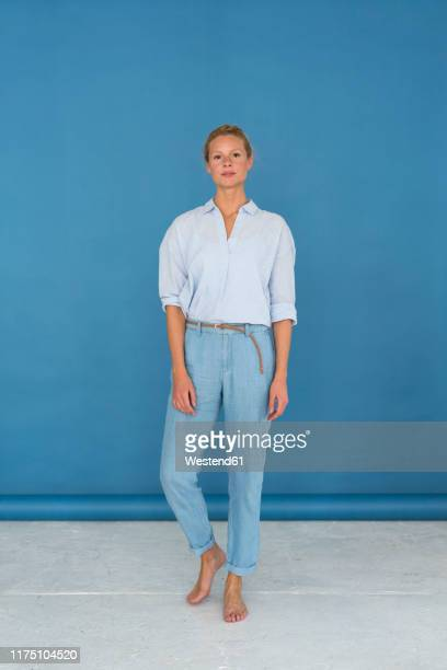 beautiful blond woman, blue background - blouse stock-fotos und bilder