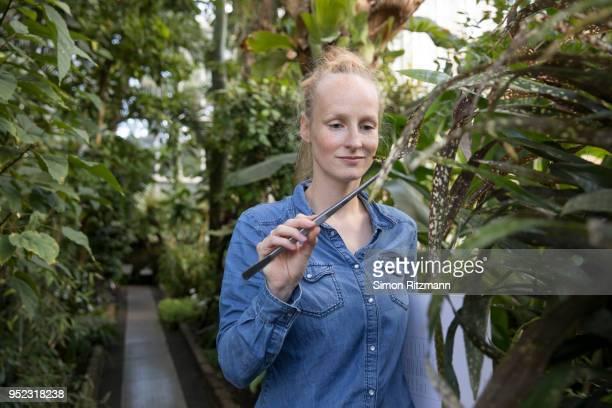 beautiful blond woman examining plant with tweezers in botanical garden - botánica fotografías e imágenes de stock