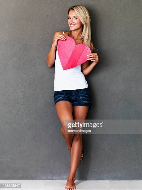 Beautiful blond woman holding a heart