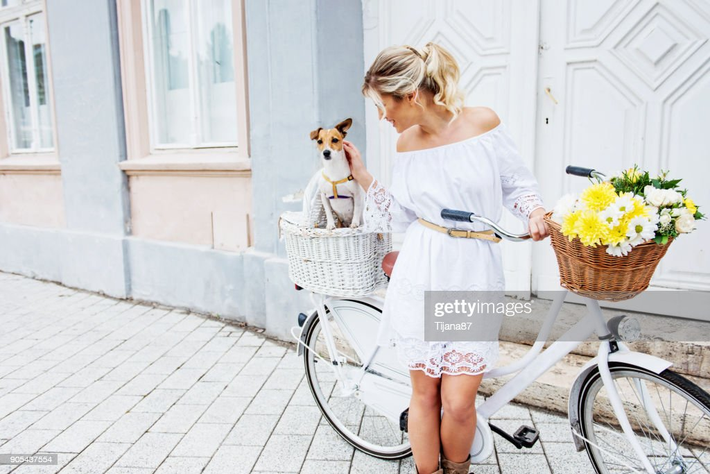 Beautiful, blond woman riding a bicycle in a town : Stock Photo