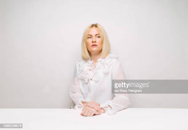 Beautiful blond woman sitting at white table