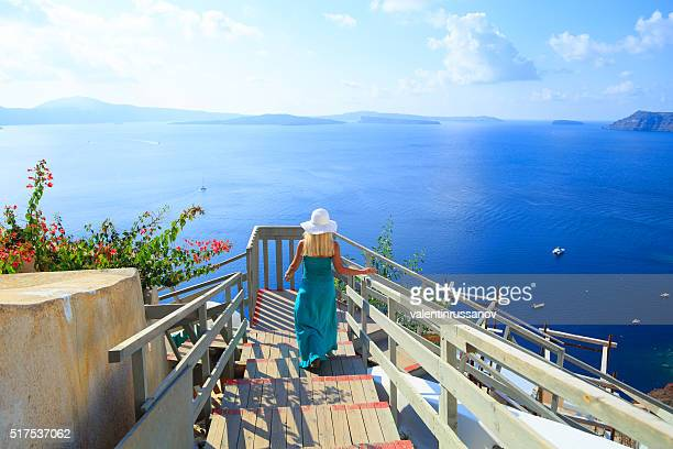 Beautiful blond woman walking in the old town of Oia