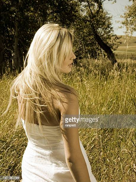 beautiful blond woman walking through wild grass - bleached hair stock photos and pictures