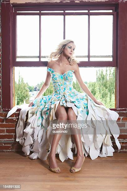 Beautiful Blond Fashion Model in Paper Couture Dress on Window