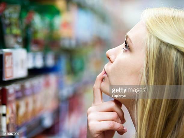 Hermosa rubia confundido por la amplia selección de productos en supermercado