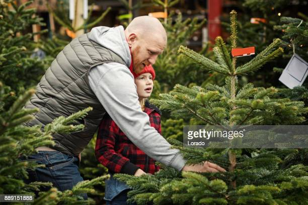 Beautiful blonde daughter and bearded redhead father shopping for a christmas tree at winter christmas market