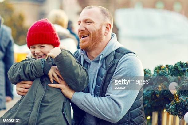 A beautiful blonde daughter and redhead father at winter christmas market