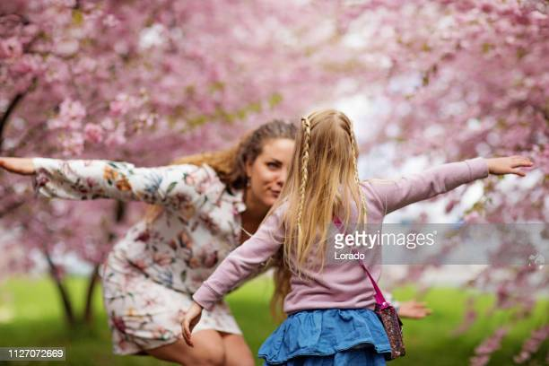 beautiful blonde dutch mother and child daughter together in a cherry blossom forest - aunt stock pictures, royalty-free photos & images