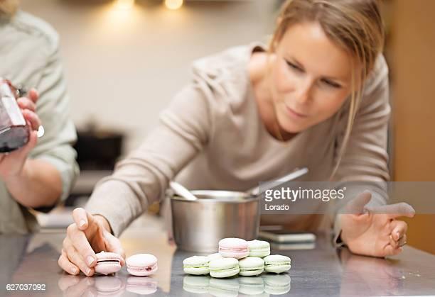 Beautiful blonde female woman baking sweets in stylish european kitchen