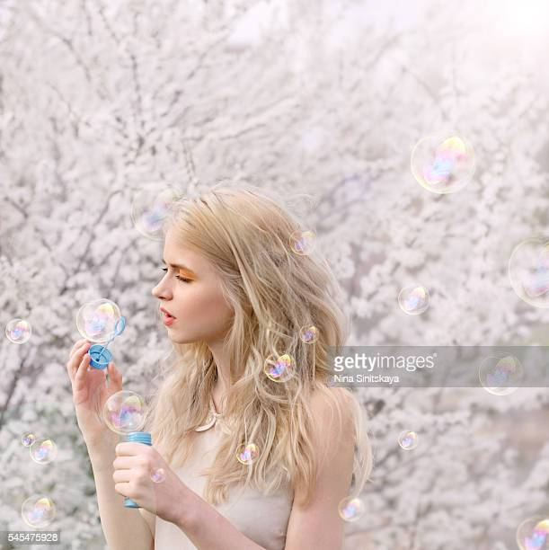 Beautiful blonde girl blowing soap bubbles in blossom