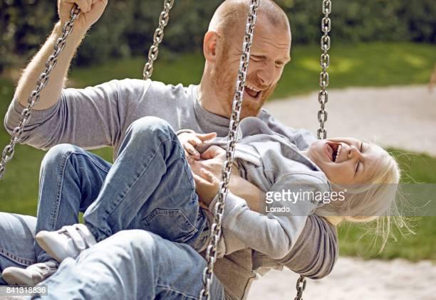 Mooie Blonde meisje kind spelen op schommel buiten met haar vader in overdag tuin