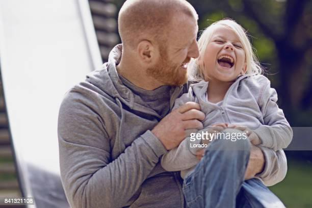 Mooie Blonde meisje kind spelen buiten met haar vader in overdag tuin
