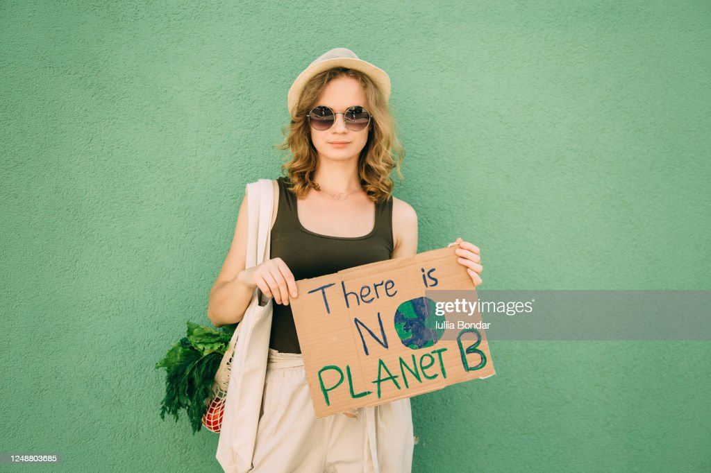 Beautiful blonde girl holding THERE IS NO PLANET B over green background : Stock Photo