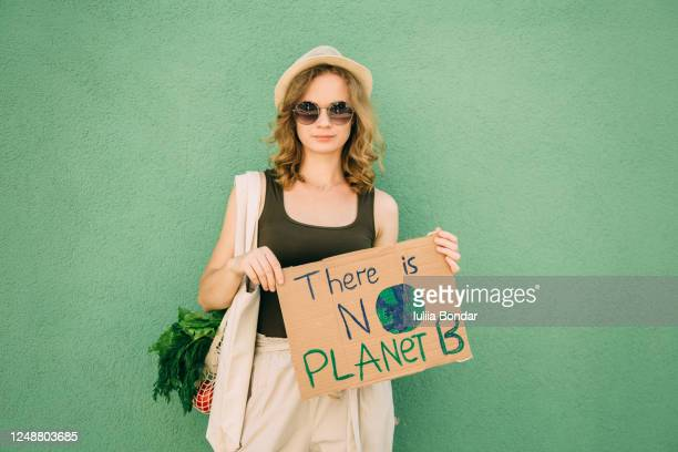 beautiful blonde girl holding there is no planet b over green background - sustainability stock pictures, royalty-free photos & images