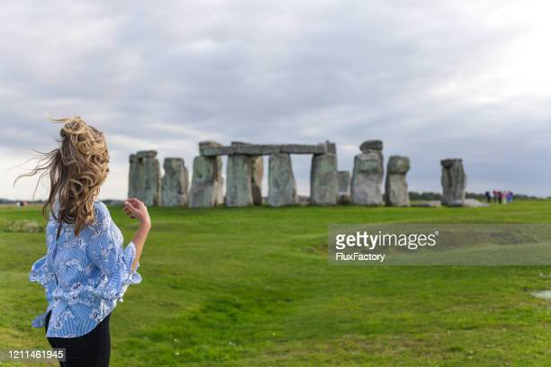 beautiful blonde girl looking at stonehenge - stonehenge stock pictures, royalty-free photos & images
