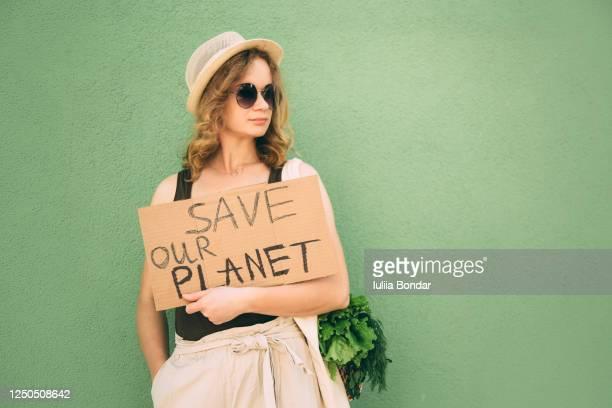 beautiful blonde girl showing save our earth - ecosistema fotografías e imágenes de stock