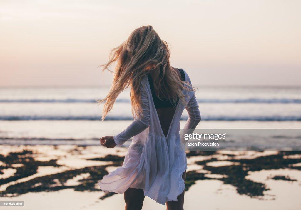 Mooi blonde meisje met lang haar Kortom witte jurk dansen bij zonsondergang : Stockfoto