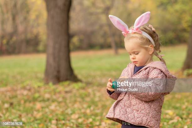 beautiful blonde haired blue eyed little girl with bunny ears holding easter eggs in the park. - easter photos stock pictures, royalty-free photos & images