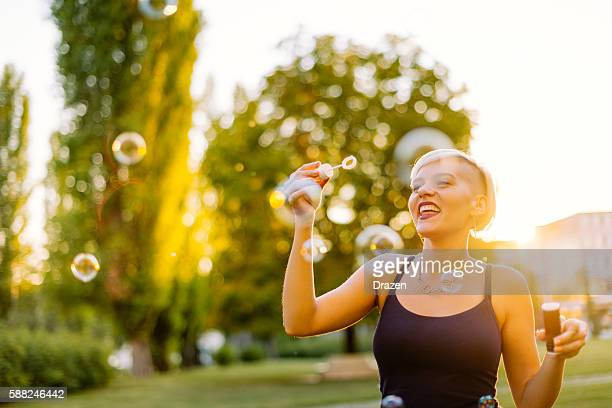 beautiful blonde hipster blowing bubbles in park - mental wellbeing stock pictures, royalty-free photos & images