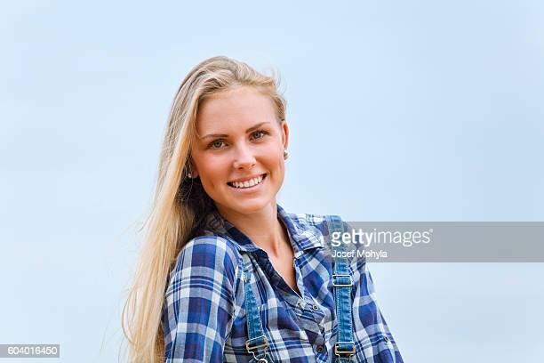 Beautiful blonde in blue shirt against blue sky