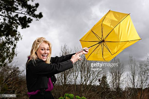 Beautiful blonde laughs as wind blows umbrella inside out