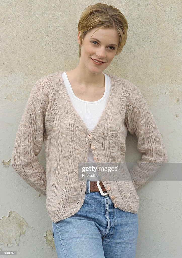 Beautiful blonde leaning against a wall : Stockfoto
