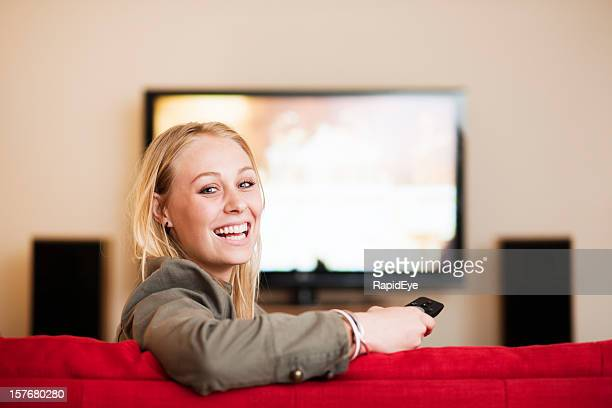 Beautiful blonde looks round from television  and smiles