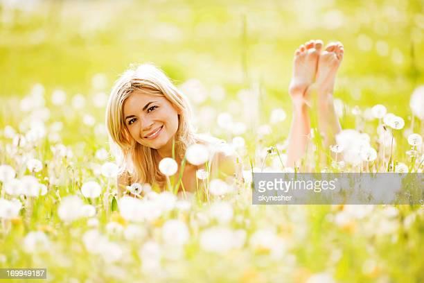 Beautiful blonde lying in the field of dandelions.