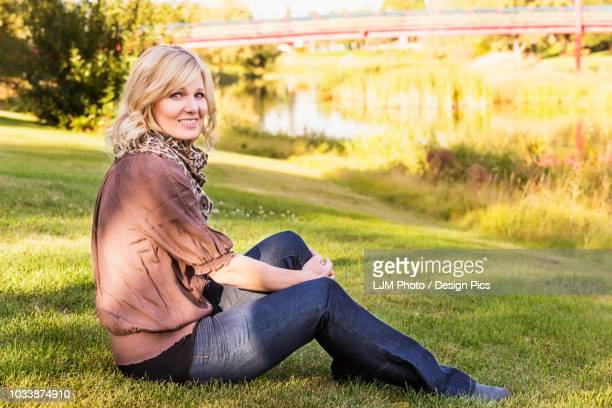 a beautiful blonde middle-aged woman poses for the camera while relaxing beside a river in a park on a warm fall evening - hot women pics stock pictures, royalty-free photos & images