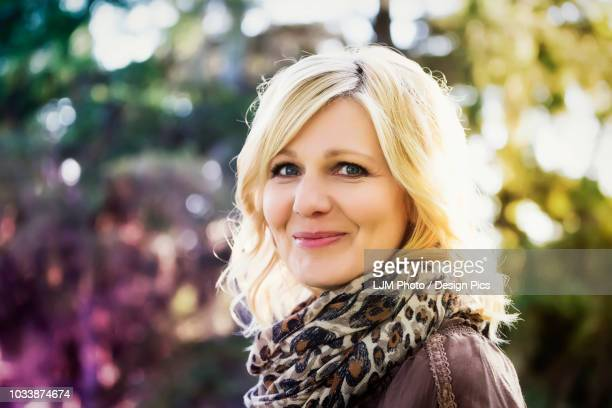 A beautiful blonde middle-aged woman poses for the camera while spending time in a park on a warm summer evening