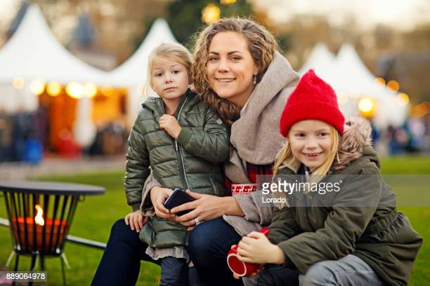 beautiful blonde mother and two blonde daughters at winter christmas market - traditional festival stock pictures, royalty-free photos & images
