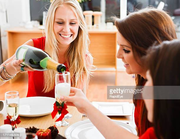 Beautiful blonde pours champagne for her Christmas dinner guests