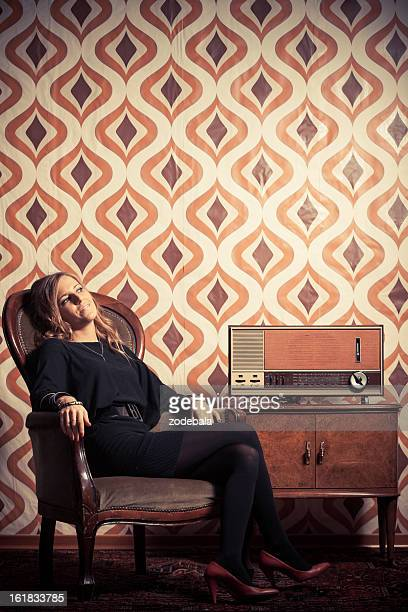 beautiful blonde retro woman listening music on vintage radio - legs and short skirt sitting down stock pictures, royalty-free photos & images