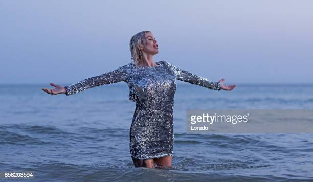 beautiful blonde scandinavian woman standing in sea in silver dress - silver dress stock pictures, royalty-free photos & images