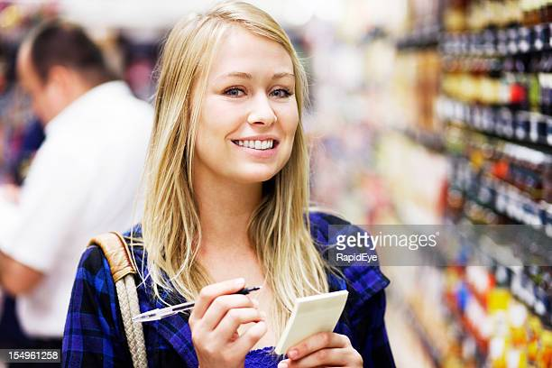 Beautiful blonde shopper, checking her list, smiles at camera