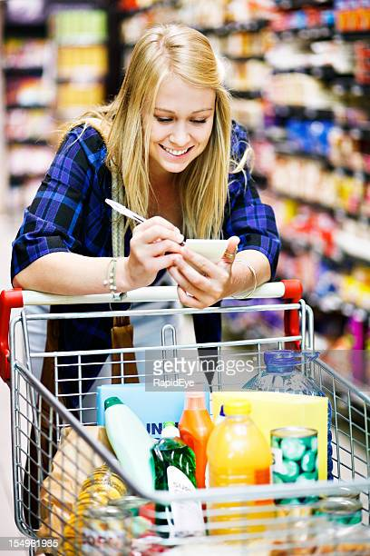 Beautiful blonde shopper in supermarket checks her shopping list