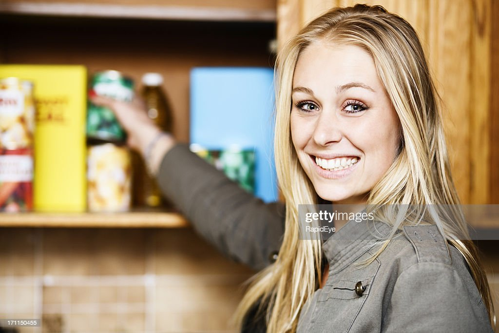 Beautiful blonde smiles as she reaches into grocery cupboard : Stock Photo