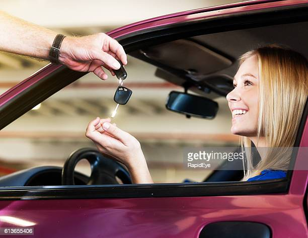 beautiful blonde smiles in delight, receiving her new car keys - recebendo - fotografias e filmes do acervo