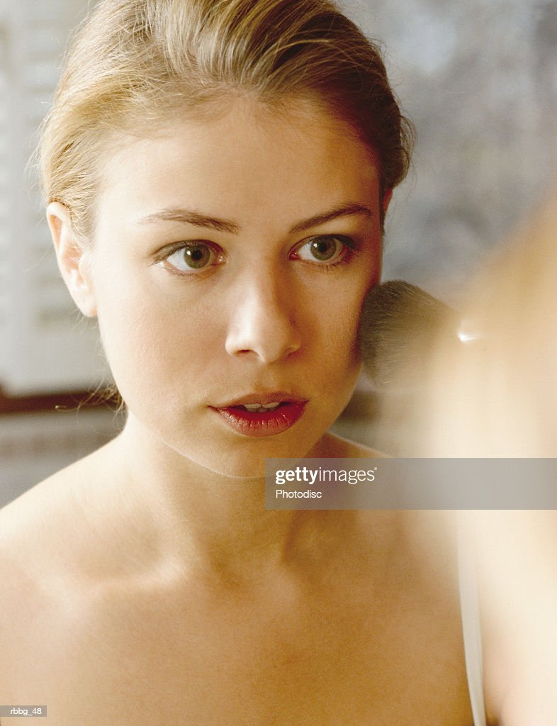 Beautiful blonde staring at her reflection : Stockfoto