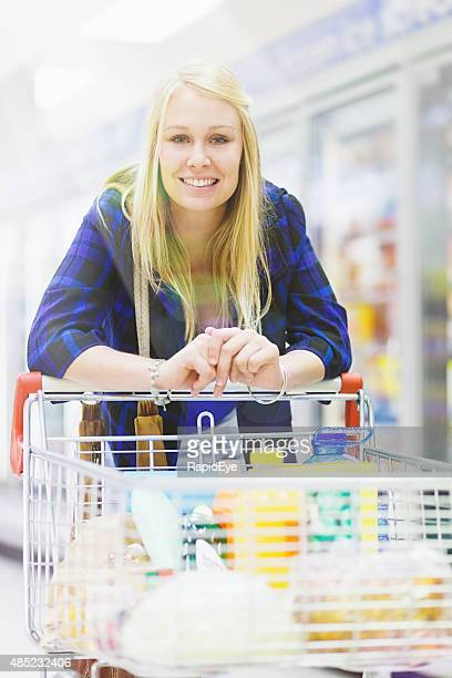 Beautiful blonde supermarket shopper leans over her shoppng cart, smiling