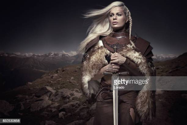 beautiful blonde sword wielding viking warrior female - warrior person stock photos and pictures