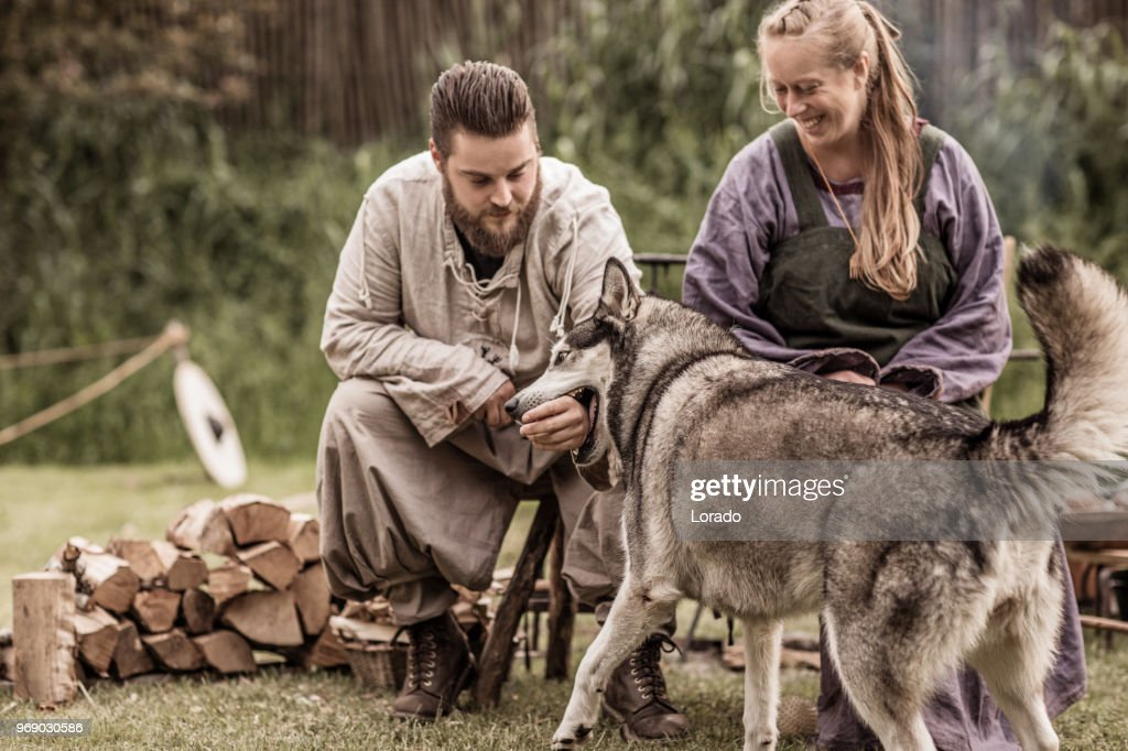 Beautiful Blonde viking warrior female sitting with a handsome bearded male soldier and a wolf in a traditional campsite : Stock Photo
