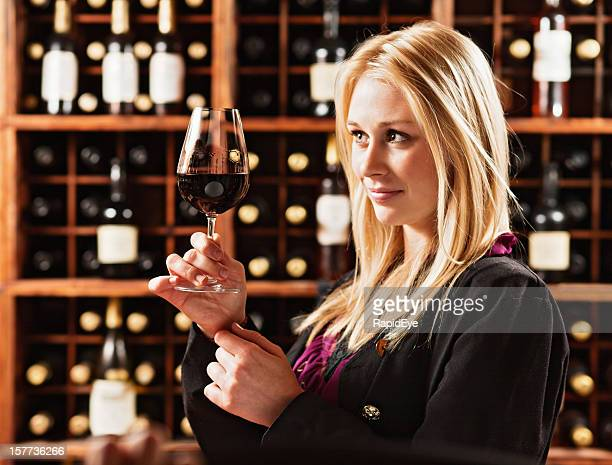 Beautiful blonde winetaster checks color and clarity of red wine