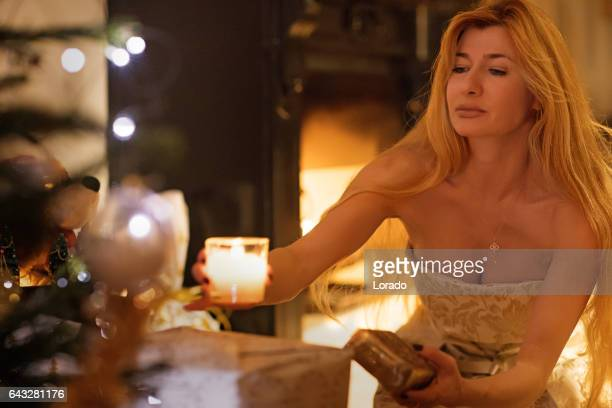 Beautiful blonde woman in christmas scene with festive decorations in indoor setting