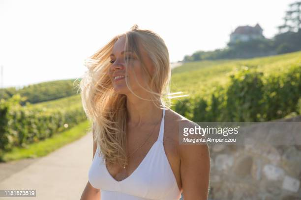 beautiful blonde woman in white dress at the vineyards of lavaux - long dress stock pictures, royalty-free photos & images