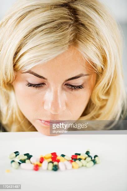 Schöne blonde Frau auf der Suche auf dem Haufen von Pillen.