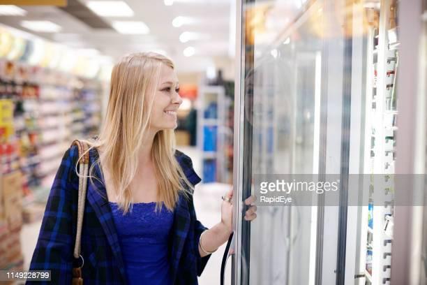 美しいブロンドの女性は、スーパーマーケットの冷蔵庫のドアを開く - 冷凍庫 ストックフォトと画像