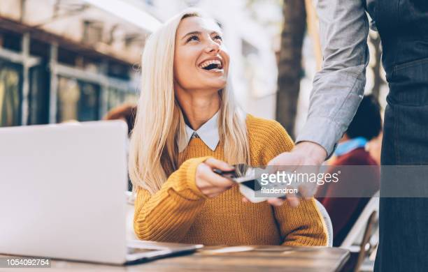 beautiful blonde woman paying contactless with smart phone - contactless payment stock pictures, royalty-free photos & images
