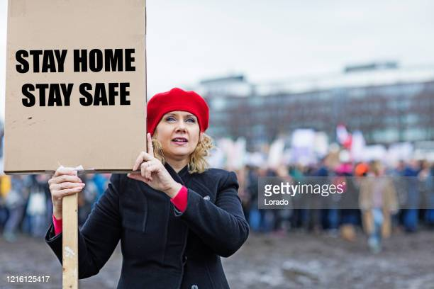 beautiful blonde woman protester during covid-19 crisis - placard stock pictures, royalty-free photos & images